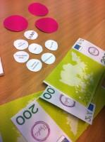 Kuva 3: Vyyhtipelin testaamista varten työstettyjä Vyyhtirahoja ja pylpyröitä. Peliä testattiin neljästä A4-kokoisesta osasta teipatulla versiolla.